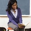 Teacher reading a book to children in a classroom