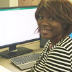 Benita Adoghe, a sophomore in Schoolcraft College's Health Information Technology program poses in front of a computer station