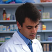 A pharmacist looks down at his chart in a backdrop of shelves with prescriptions on them
