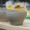 A set of ceramic pottery bowls in the making sit on a table