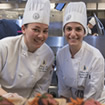 Two female chefs pose for a photo while they prepare many plates in a kitchen