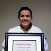 Chef Heather holds her framed certification award with a smile