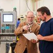 An instructor guiding a student in a manufacturing setting