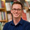 Michael Gustafson stands within a bookstore and shelves of books in backdrop