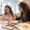 Two young female students study together in group in a library setting