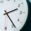 Close up view of the hands of a clock on a pale blue wall