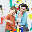 A female adult smiles as she watches a young boy paint a mural on paper in activity