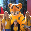 Three female students and an Ocelot mascot pose in a group photo