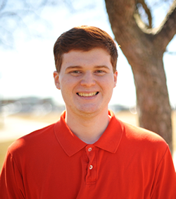 A professional headshot photo of Daniel Arini, a young student smiling in a summer backdrop outdoors