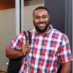 Schoolcraft student smiling with backpack in a red, white and blue plaid shirt