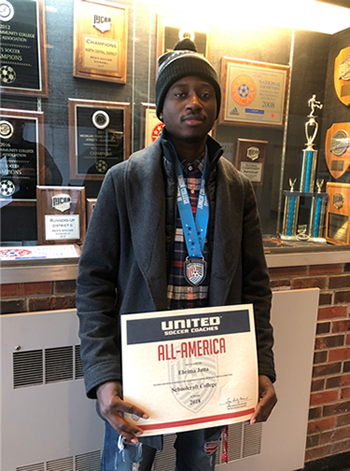 "Soccer player Ebrima Jatta holds a certificate in front of a trophy showcase that reads ""All-American"" title"