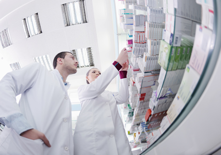Two Pharmacy Technicians studying prescription packages on a shelf display
