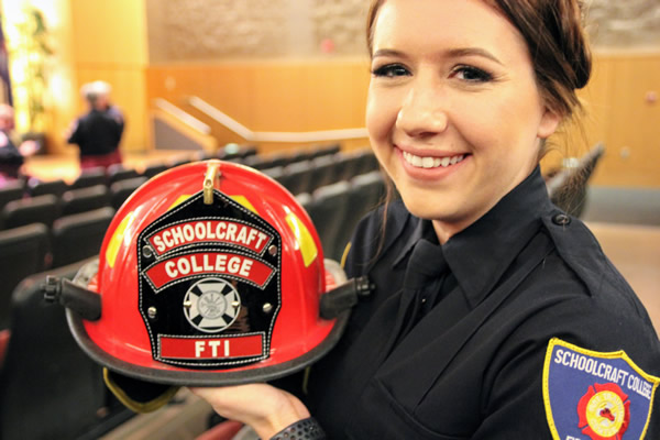 A fire academy graduate posing with a fire hat