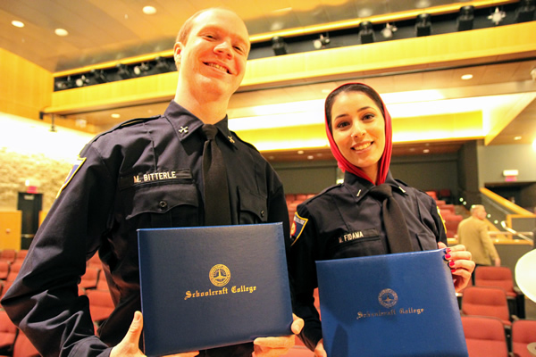 Two fire academy graduates proudly posing for the camera