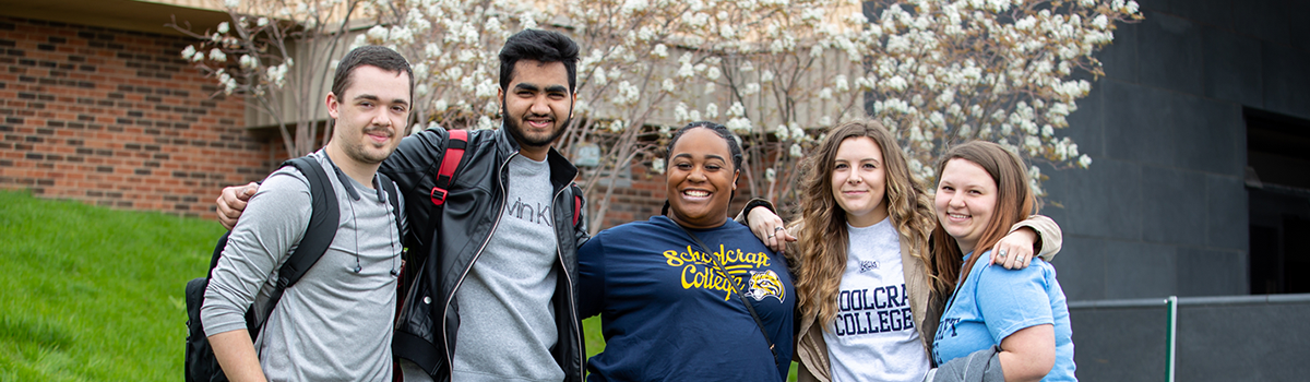 Community College Students pose for a picture outside on a spring day