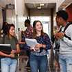 Three students converse in a college hallway and are holding class books