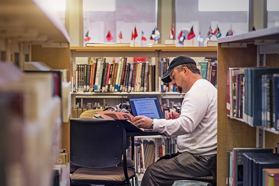 A student studies on his laptop at a table surrounded by books in a library