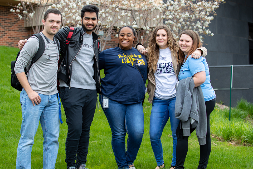 Five students pose for a group photo outside a campus building