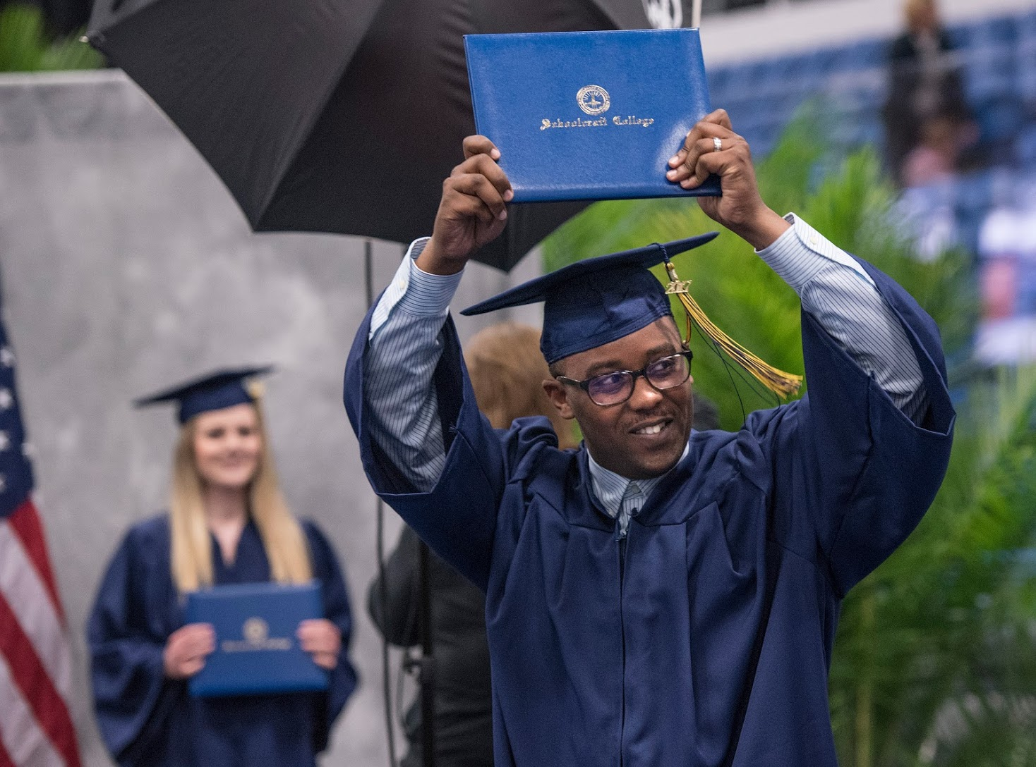 Student proudly holds up his diploma during graduation commencement
