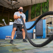 A male wearing a face covering doing ropes at the fitness center