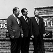 Old black and white photo of three men at the Schoolcraft College sign
