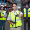 Three male workers where bright vests in a warehouse setting