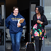 Two female students talk as they walk outside of a building with their school books in hand