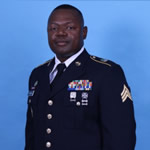 Portrait photo of Timothy Brown II in National Guard uniform with various pins and patches on the dark blue coat.