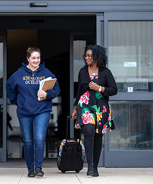 Two female students talking as they walk out of a building with books in hand