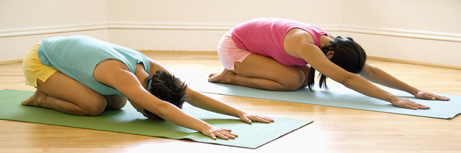 Two women do a yoga pose on a mat