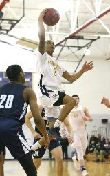 A Schoolcraft player jumps high and with reach for a basket