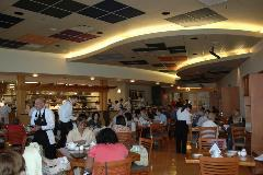 Wide angle view of the American Harvest indoor dining area with a full house of activity