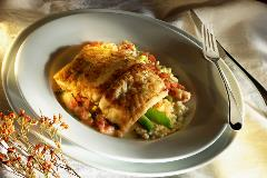 An artistic culinary dish of fish over a creamy side