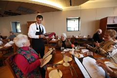 A male server notes orders at a table seated with three women looking at menus