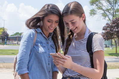 Two young women students look at their phone outdoors campus on a sunny day
