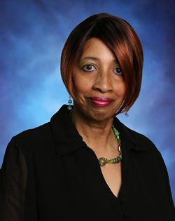 Headshot of Carmen Wilson with a blue backdrop