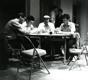 A stage scene of men playing cards at a table.