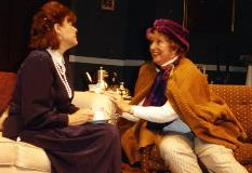 Two actresses talking on a stage set.