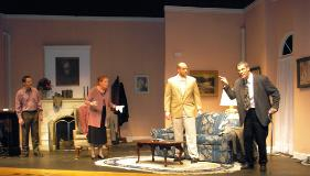 A stage scene of multiple actors interacting in a living room set.