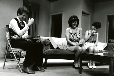 Three actors laughing in a living room stage set