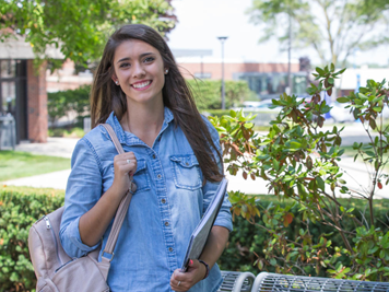 A young female student smiling and holding class books, standing outside with greenery campus backdrop