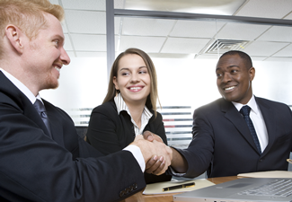 A team business meeting in a corporate setting and two men shake hands