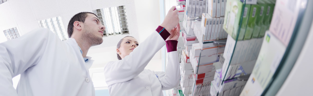 Two Pharmacy Technicians looking at a shelf of medications
