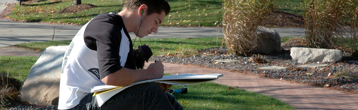 Photo of a student drawing outside