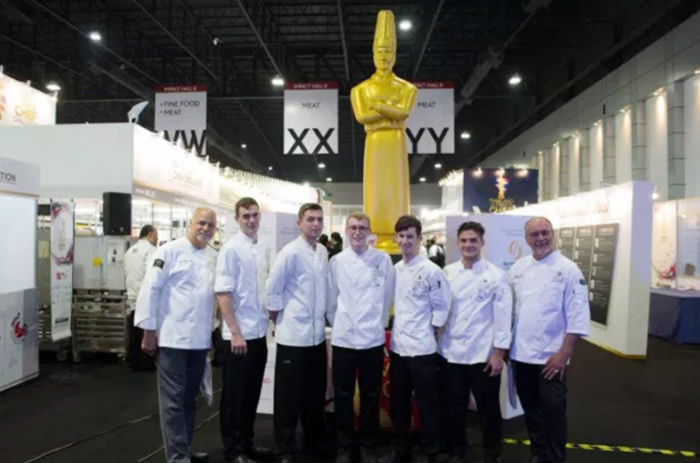 Group photo of the culinary arts team in front of a culinary chef statue